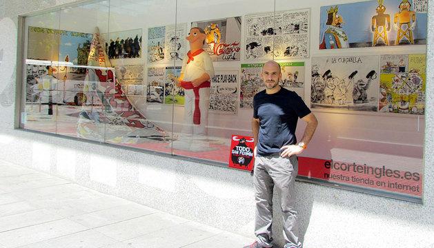 Oroz, frente al escaparate elaborado con una representación de las viñetas de su libro 'Todo San Fermín'.