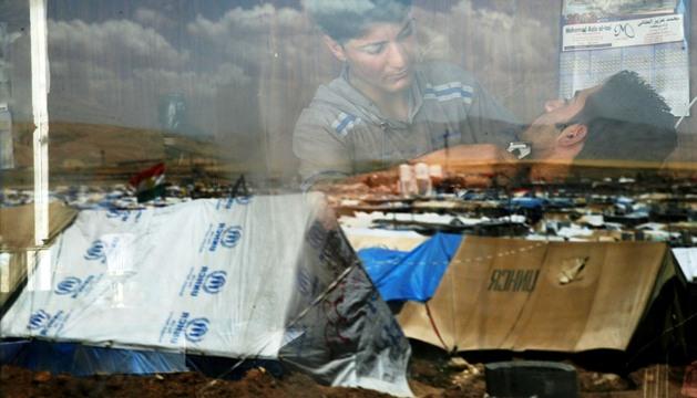 El campo de refugiados sirios-kurdos de Domiz se refleja en el cristal de una barbería.