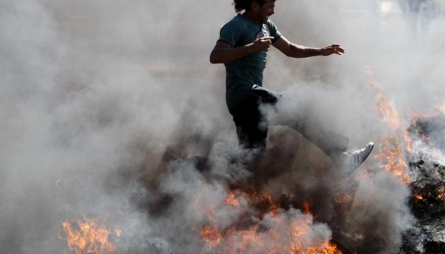 Un manifestante salta sobre una barricada de fuego durante una protesta en Brasilia (Brasil).