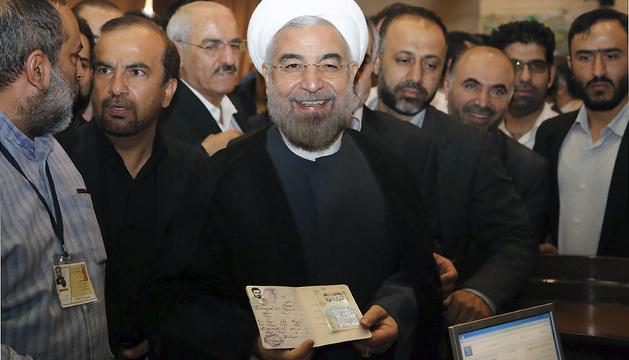 El candidato presidencial Hasan Rohani (dcha) muestra su pasaporte antes de ejercer su derecho al voto en la mezquita Imam-Reza, en Teherán.