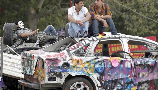 Dos activistas conversan este sábado sobre un coche, a la entrada del parque de Gezi, en Estambul.