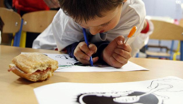 En la ludocteca de Cruz Roja, un niño colorea un dibujo con la ilustración de Oroz para la campaña 'Esta va por ti'.