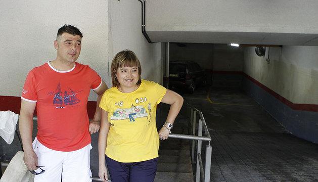 Javier Bazán Pastor y Kristina Busto Lezáun, el viernes, a la entrada del garaje. Marcado con una flecha, el nivel que alcanzó el agua.