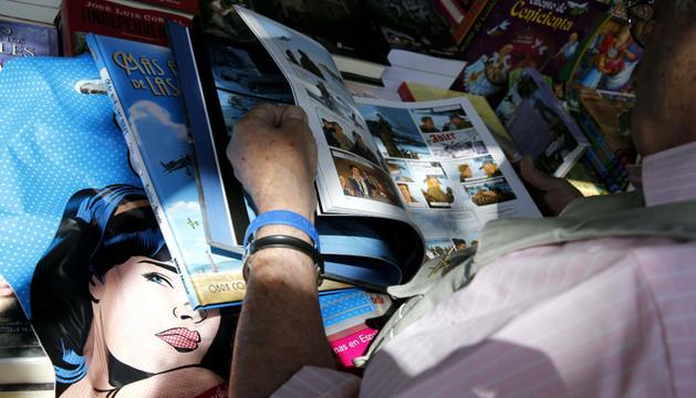 Una persona lee un cómic en la feria del Libro de Madrid