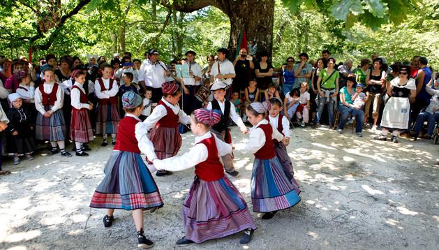 Un corro de niños interpretando danzas tradicionales.