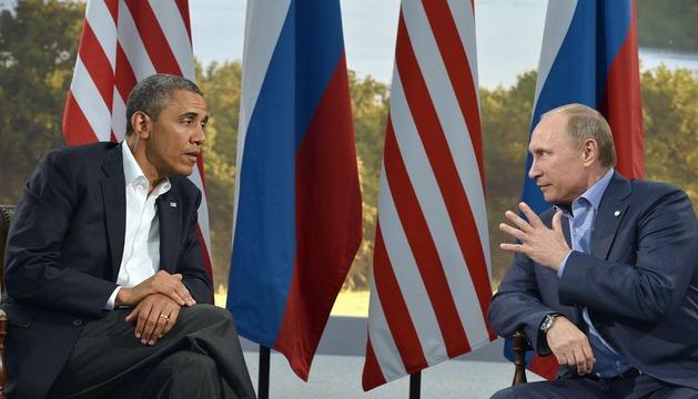 Vladimir Putin (d) habla con Barack Obama durante el primer día de la cumbre del G8