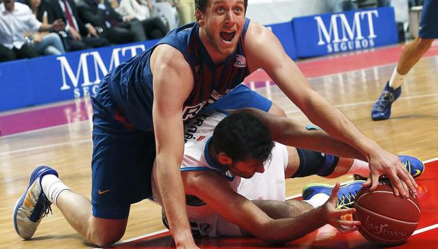 El alero del Real Madrid, Rudy Fernández (abajo), lucha el balón con el australiano Joe Ingles, del FC Barcelona Regal