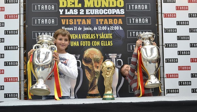 Dos niños levantan las dos Eurocopas conseguidas por España durante la exposición en el Centro Comercial Itaroa