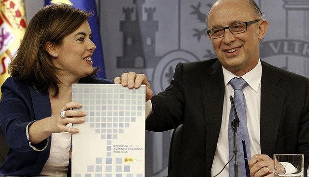Soraya Sáenz de Santamaría y Cristóbal Montoro sostienen el informe con las reformas.