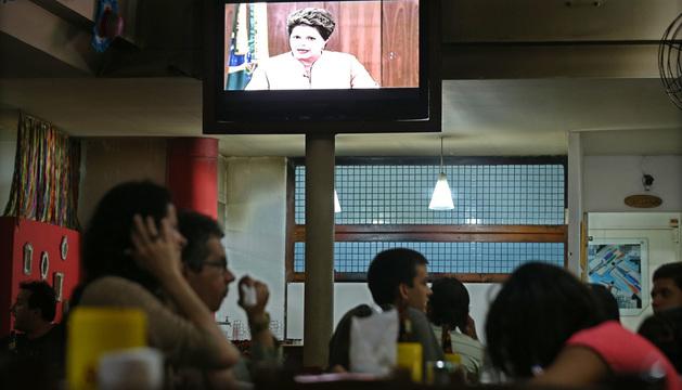 Los ciudadanos observan la emisión del mensaje de la presidenta Dilma Rousseff en un local de Salvador, Brasil.