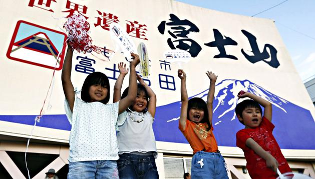 Cuatro niños sostienen carteles y adornos durante uno de los actos de celebración por el monte Fuji