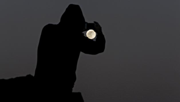 Una persona fotografía la Luna desde la isla de Tenerife