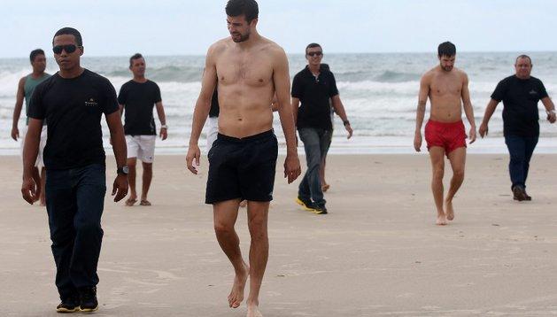 Los jugadores de la selección española de fútbol Gerard Piqué (c) y Cesc Fábregas (d) caminan junto con miembros del equipo de seguridad en la playa de Futura, a las afueras de Fortaleza (Brasil)