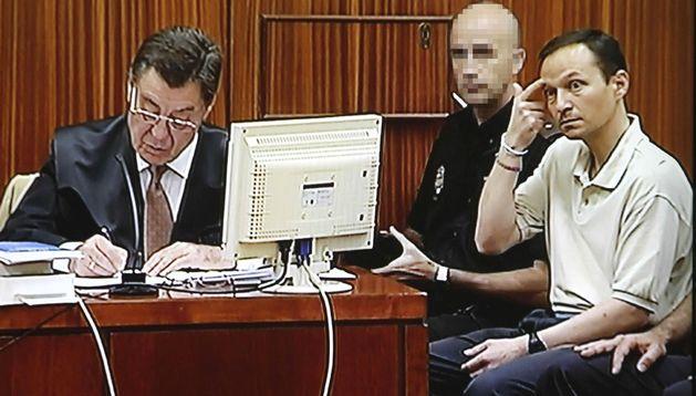 Fotografía tomada del monitor de televisión en la que aparece José Bretón (d).