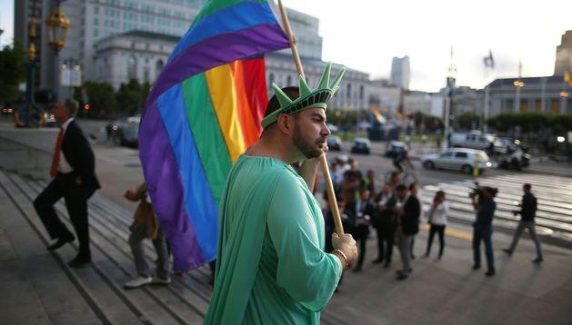 Un activista homosexual vestido de la Estatua de la Libertad sostiene una bandera.