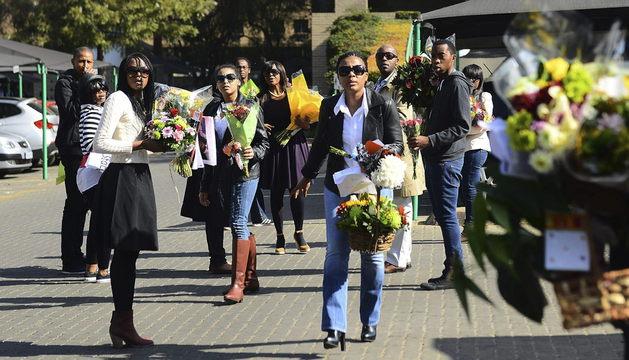 Tukwini Mandela (centro), hija de Nelson Mandela, lleva flores entregadas por sus simpatizantes junto a otros familiares