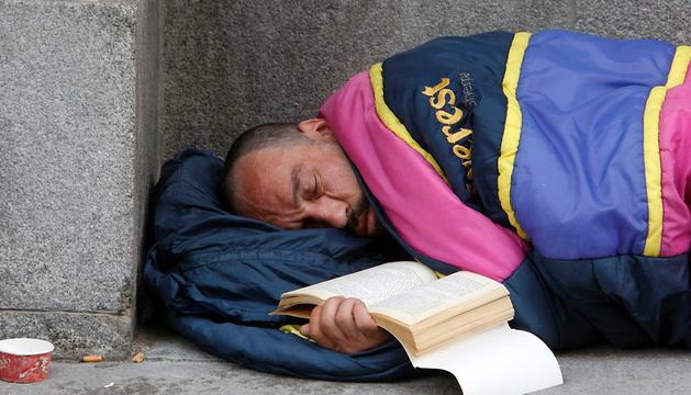 Un hombre sin techo duerme en una calle de Madrid.