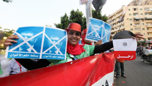 Una mujer sostiene carteles contra el presidente, Mohamed Mursi, durante una protesta en El Cairo