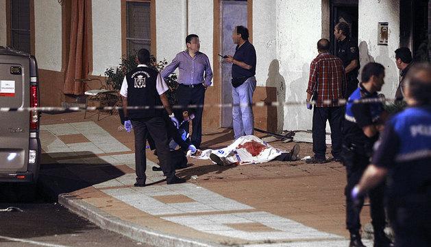 Policías y forenses junto al cuerpo hallado por los bomberos.