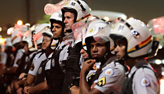Un grupo de policías se para frente a los manifestantes que protestaban este lunes, exigiendo mayor inversión pública en educación y salud, en Brasil.