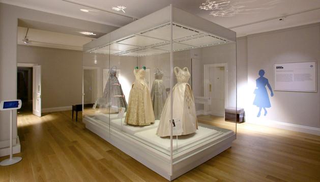 Fotografía facilitada por la Fundación Historic Royal Palaces que muestra varios de los trajes que la Reina Isabel ha lucido y que forman parte de la muestra