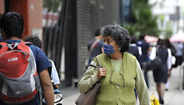 Una mujer se cubre con un tapabocas mientras camina este jueves 4 de julio de 2013, en Ciudad de México (México).