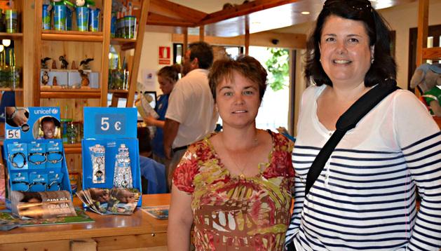 Ana Marta Torres, directora ejecutiva de Sendaviva; y Maider Gabilondo, coordinadora de UNICEF Comité Navarra, con merchandising de la organización.