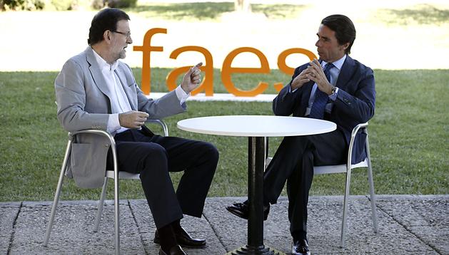 El presidente del Gobierno, Mariano Rajoy, conversa con el expresidente del Gobierno y presidente de la fundación FAES, José María Aznar (d), momentos antes de su intervención en el acto de clausura del campus de verano de la fundación FAES
