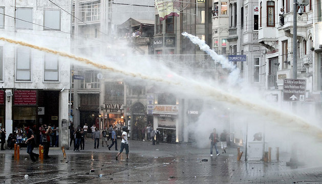 Varios manifestantes y transeúntes evitan los chorros de agua a presión de la Policía durante una concentración.