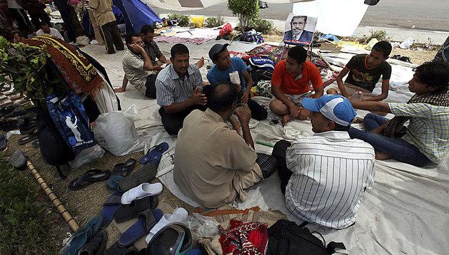 Numerosos simpatizantes del depuesto presidente Mohamed Mursi permanecen sentados en el suelo durante una protesta en apoyo a Mursi, a las puertas de la mezquita de Rabaa al Adauiya en El Cairo.