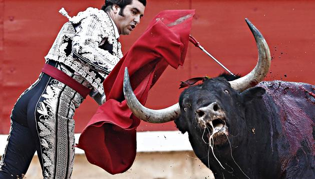El torero Morante de la Puebla entra a matar a su primero de la tarde durante la cuarta de abono de la Feria del Toro de los Sanfermines 2013 donde compartió cartel con Julian López