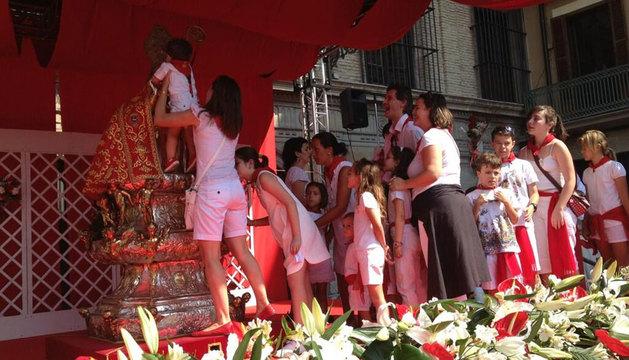 Los niños besan al santo.