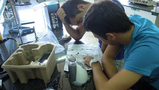 Dos jóvenes analizan un aparato para desarrollar un experimento