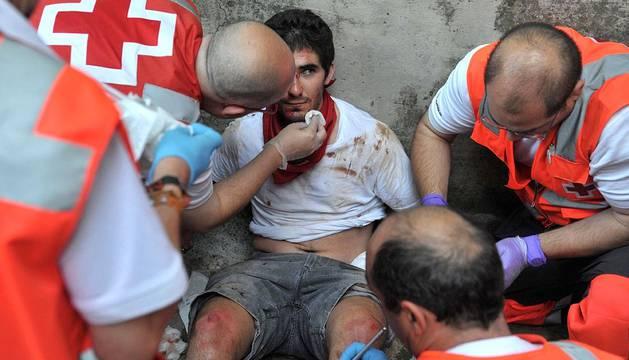 La Cruz Roja atiende a los heridos en la bajada del callejón de la plaza de toros de Pamplona durante el séptimo encierro de los sanfermines 2013. Un corredor ha resultado herido muy grave.