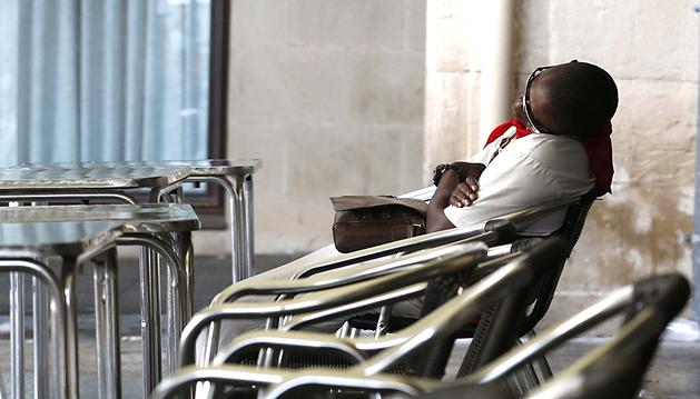 Un mozo duerme en una terraza de la Plaza del Castillo