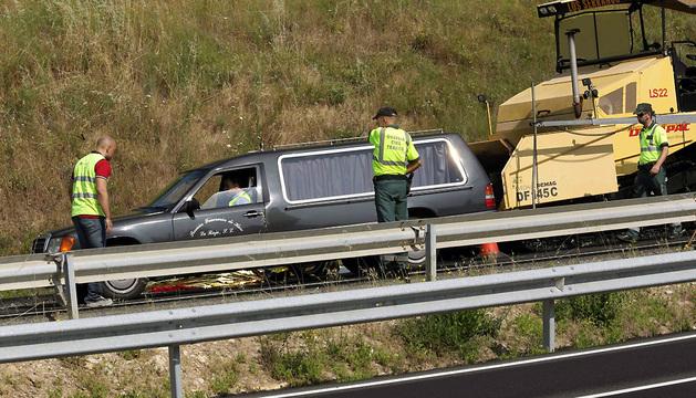 Los coches de la funeraria recogen los cuerpos de las dos personas fallecidas esta mañana en la AP-68 tras ser atropelladas por un turismo.