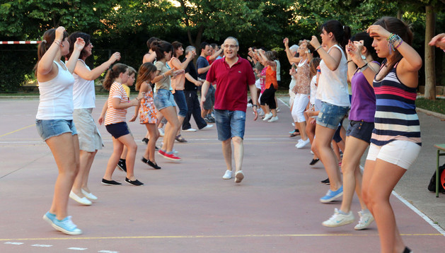 Los participantes en el curso de danzas ensayan un baile bajo la dirección de Juan Sáinz, en el centro, en el patio del colegio Elvira España.
