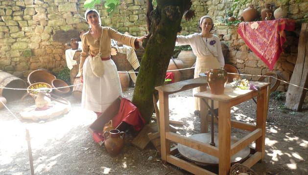 LAS BODEGAS, TAMBIÉN ABIERTAS.  Amaya Zabaleta Mendaza, a la izquierda, junto a Ana Cadarso García, en el rincón del alfarero que sirvió de antesala a la bodega de sillería abierta en el subsuelo de esta misma vivienda de Bargota.