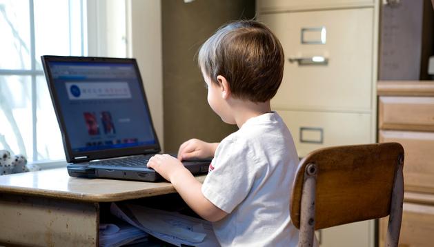 Un niño con un ordenador portátil en su casa