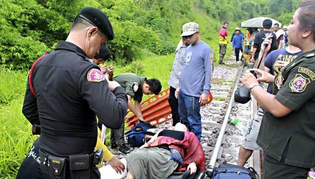 Miembros de los servicios de emergencia atienden a uno de los turistas extranjeros heridos tras descarrilar un tren en Den Chai, en el norte de Tailandia este miércoles.
