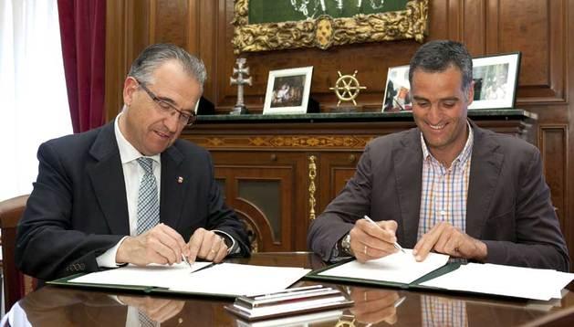 Enrique Maya y el presidente de la Fundación Miguel Induráin, Prudencio Induráin, firmando el convenio para el apoyo a deportistas de alto nivel.
