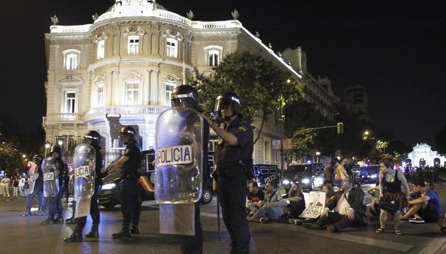 Agentes antidisturbios vigilan a los manifestantes a su paso por la plaza de Cibeles, en Madrid, tras la concentración que hubo por la tarde ante la sede del PP.
