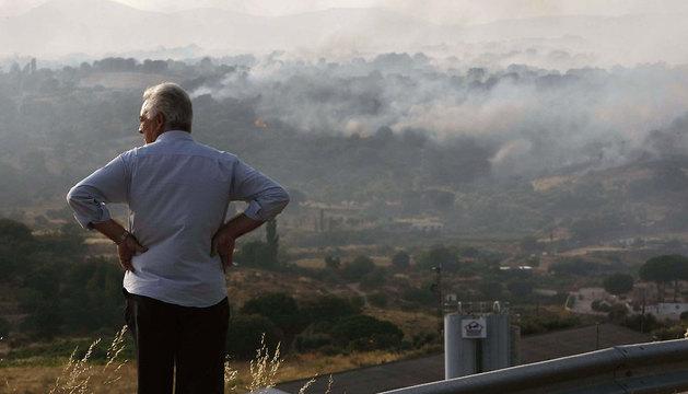 Un hombre observa las llamas del incendio forestal.