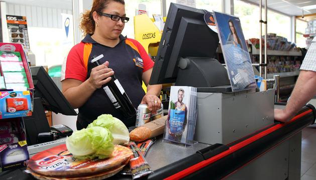 La empleada de la gasolinera Ezcaba de Villava vende a un cliente vino, cerveza, pan y pizzas, entre otros