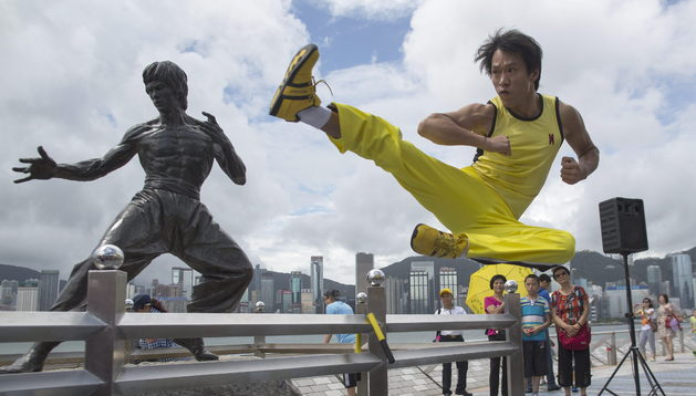 Un fan de Bruce Lee homenajea al mito frente a su estatua.