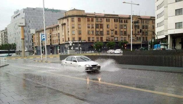 Un coche pasa por una de las balsas que se formaron en algunas calles de Pamplona