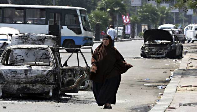 Una mujer egipcia pasa por delante de los coches destruidos durante los disturbios ocurridos este martes.