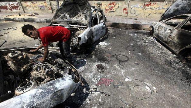 Un hombre inspecciona coches quemados tras los disturbios ocurridos en Egipto.