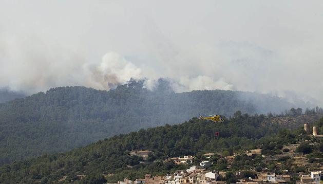 Un helicóptero trabaja en las labores de extinción del incendio forestal declarado este viernes en el municipio mallorquín de Andratx.