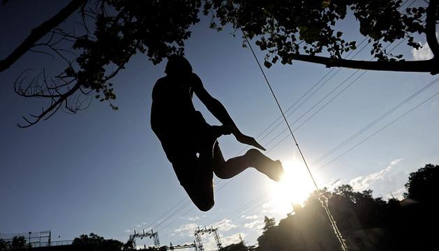 Un joven salta al río Arga a la altura del Club Natación.